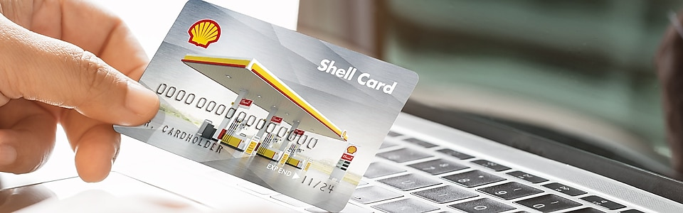 A hand holding Shell Fuel Card with card reading machine in the background