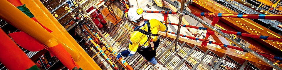 Shell employee descends down the stairs on a Prelude FLNG topside module