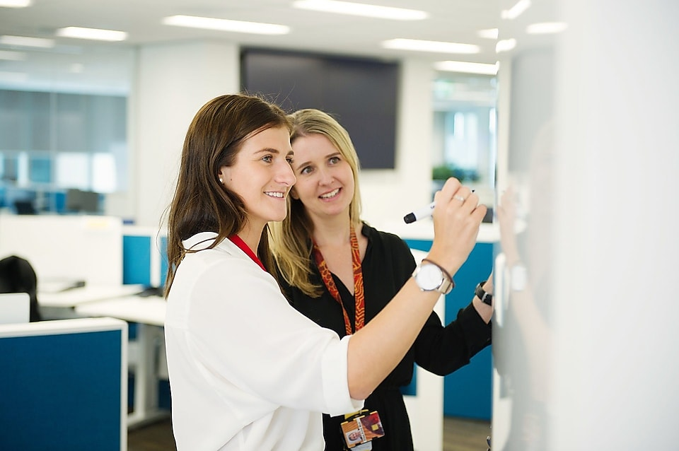 Shell Graduate Samantha Palmer writing on a whiteboard, having a discussion with her mentor Elise-Anne Muir