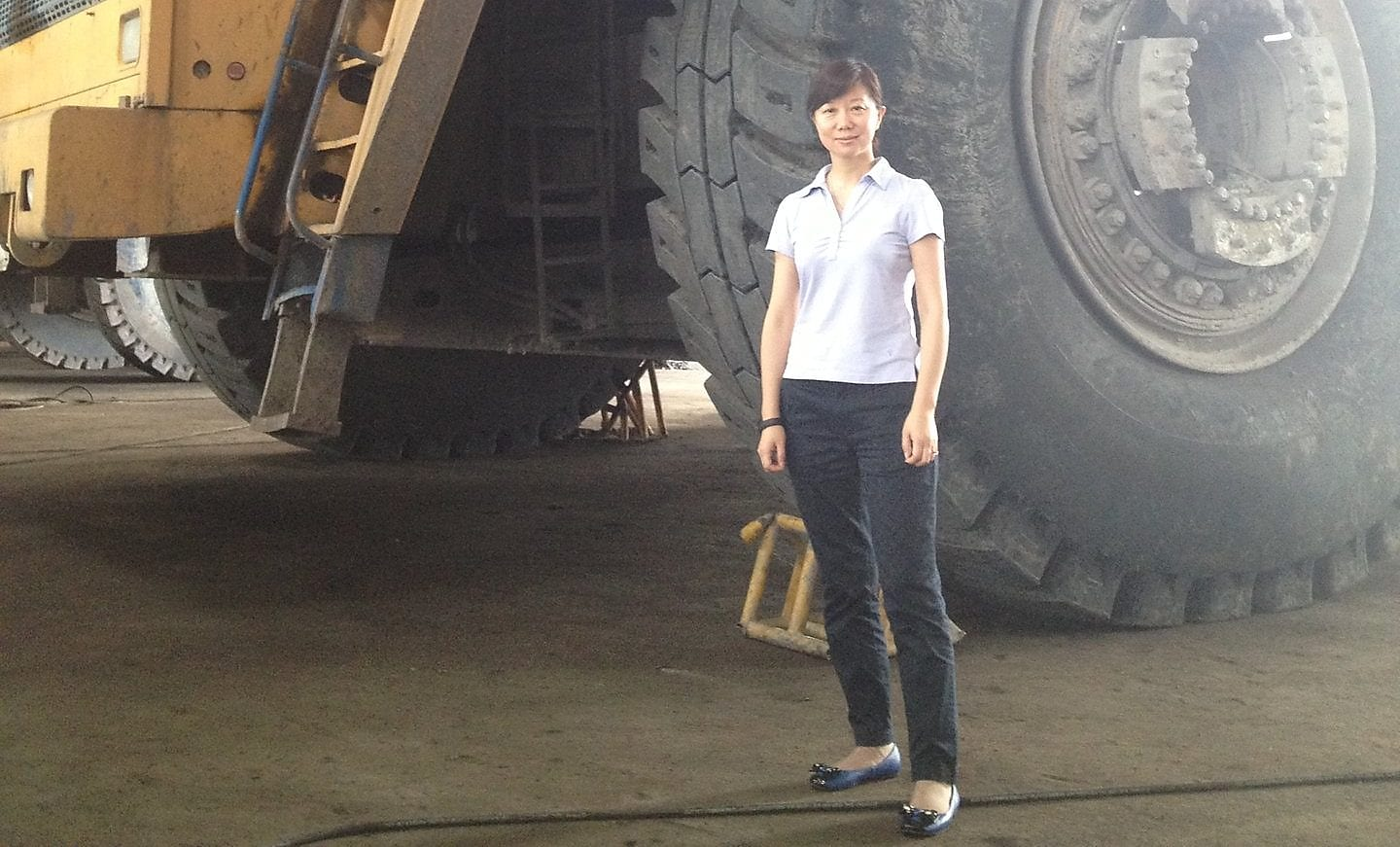 Jessica Zhu standing in front of large machinery.