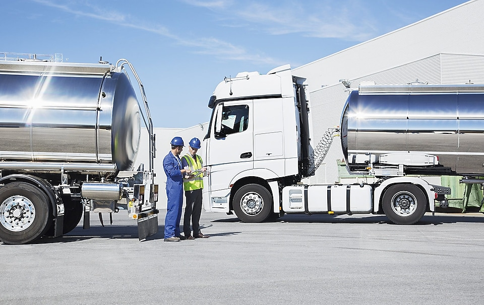 two technicians between two heavy oil trucks
